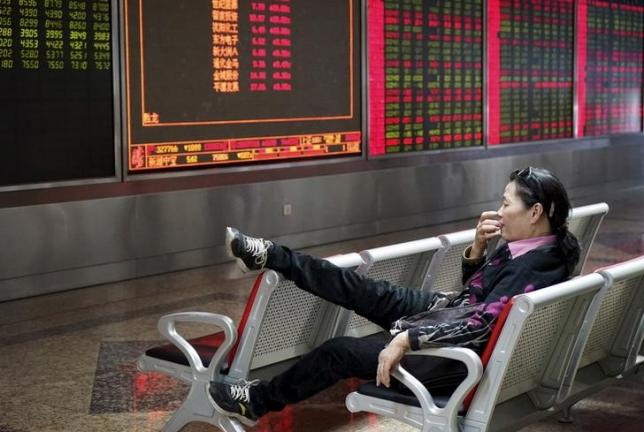 An investor rests on a chair in front of an electronic board showing stock information at a brokerage house in Beijing, China, October 13, 2015.  REUTERS/Stringer