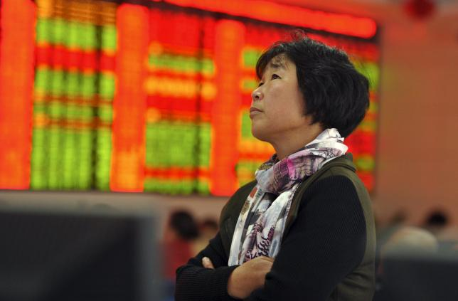 An investor stands in front of an electronic board showing stock information at a brokerage house in Fuyang, Anhui province, China, October 26, 2015. REUTERS/Stringer