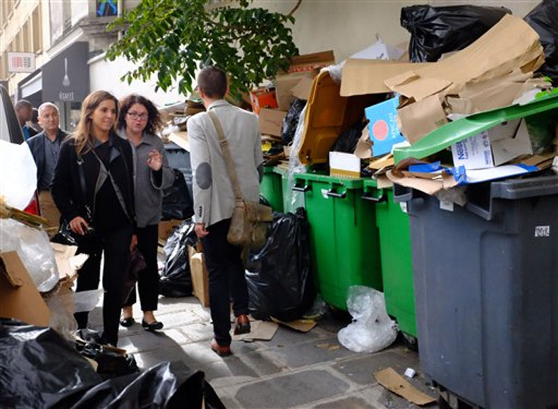 People walk past a pile of garbage during the fourth day of a garbage collectors strike in Paris, France on Thursday, October 8, 2015. Photo: Ap