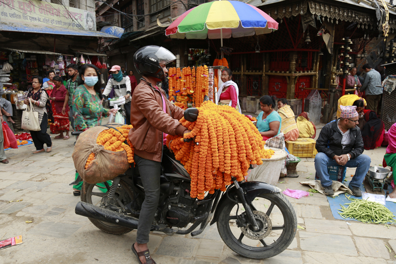 A vendor rides his bike along an Ason road with flower garlands, in Kathmandu, on Wednesday, October 14, 2015. In past years, the road would be besy in the run-up to the Dashain festival. Photo: RSS