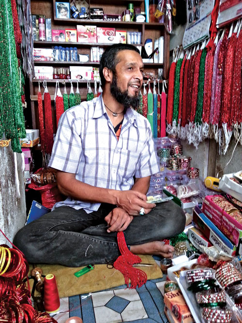 Nakim Khan, the owner of a pote (glass beads) and cosmetics shop in Mangalbazaar, talking to a customer (not seen), on Monday, October 19, 2015. Khan, who followed the footsteps of his father in taking up the trade, laments lack of interest among younger generation in giving continuity to the age-old family business. Photo: THT