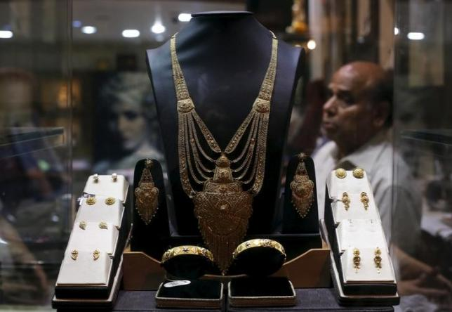 A gold necklace is displayed as a salesman waits for customers inside a jewelry showroom in the old quarters of Delhi April 21, 2015. REUTERS/Adnan Abidi