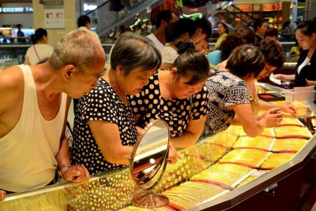 Customers look at gold necklaces at a jewelry store in Xuchang, Henan province, August 12, 2015. REUTERS/Stringer/Files