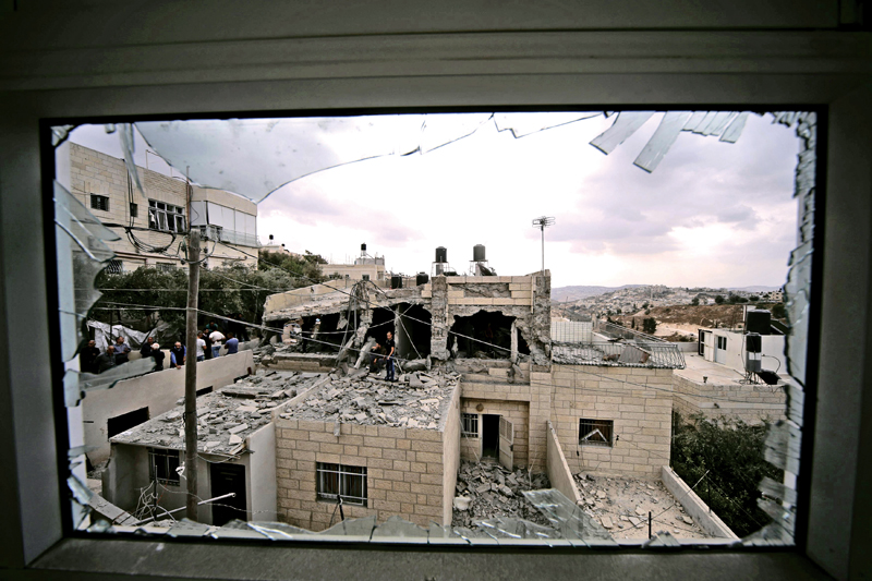 Palestinians stand on the razed home of a Palestinian militant in Jabel Mukaber, in an area of the West Bank that Israel captured in a 1967 war and annexed to the city of Jerusalem, October 6, 2015. Israeli forces destroyed the homes of two Palestinian militants and sealed off part of a third in Jerusalem on Tuesday, in a crackdown launched by Prime Minister Benjamin Netanyahu after four Israelis were killed in Palestinian attacks. The Israeli military said in a statement it had demolished the family home of the Palestinian who in November 2014 killed four rabbis and a police officer in a Jerusalem synagogue before he and another attacker were shot dead at the scene by police. REUTERS/Ammar Awad       TPX IMAGES OF THE DAY