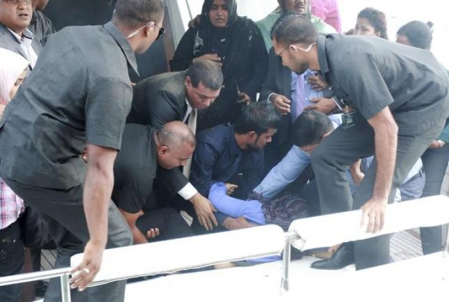 Officials carry an injured woman off the speed boat of Maldives President Abdulla Yameen (not pictured) after an explosion onboard, in Male, Maldives September 28, 2015. REUTERS/Waheed Mohamed