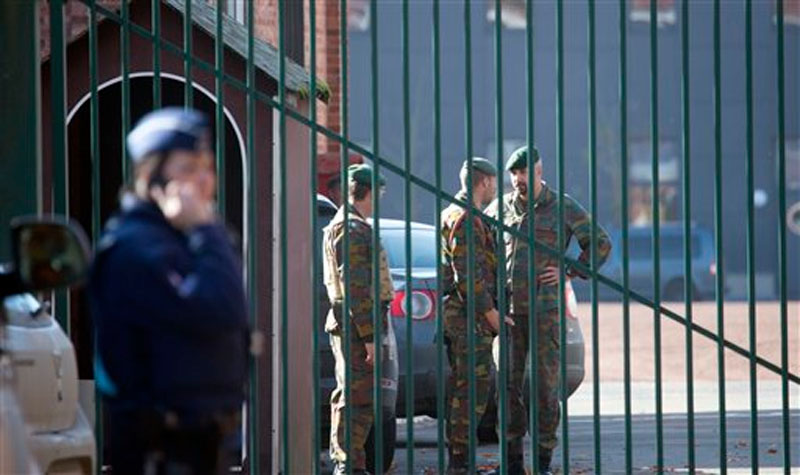Police and military personnel stand outside a military barracks in Flawinne, Belgium on Monday, October 26, 2015. Photo: AP