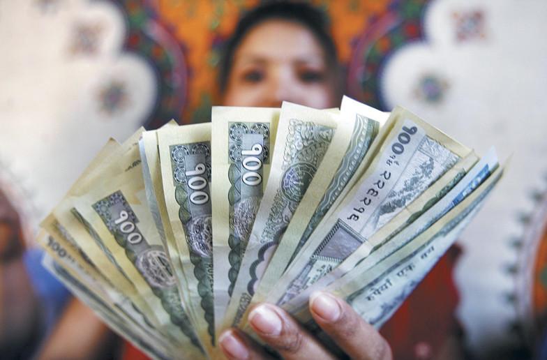 A woman shows Nepali rupee