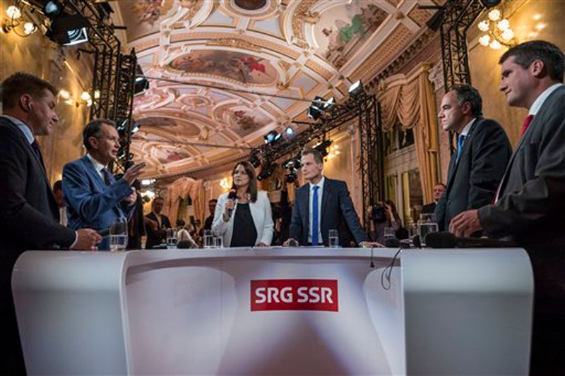 The presidents of Switzerland's leading political parties, from left, Toni Brunner right wing SVP, Philipp Mueller liberal FDP, Philipp Mueller the two TV hosts Romaine Morard and Jonas Projer, Christophe Darbellay centrist party CVP, and Christian Levrat socialist party SP, analyze the results of the national elections during a television talk in the parliament building ''Bundeshaus'' in Bern, Switzerland, Sunday, October 18, 2015. Photo: AP