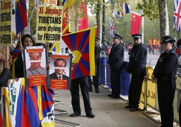 Police officers stand in front of pro-Tibet protesters as they wait on the Mall for China's President Xi Jinping to pass during his ceremonial welcome, in London, Britain, October 20, 2015.     REUTERS/Peter Nicholls