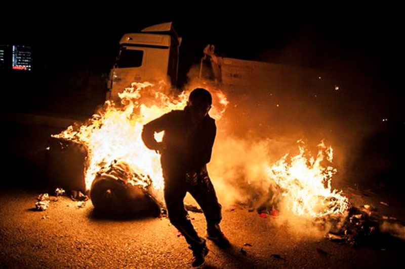 A leftist protester runs from a barricade after protesters set it on fire, during minor clashes with Turkish security forces following a protest against Saturday's Ankara bombing attacks, in Istanbul's Gazi district on Monday, October 12, 2015. Photo: AP