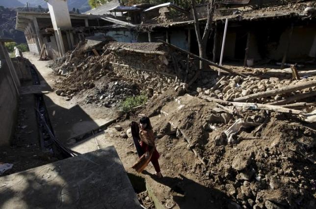 A girl runs past the debris of a house damaged by the earthquake in Rehan Kot village in District Dir, Pakistan, October 28, 2015. REUTERS/Faisal Mahmood