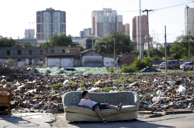 A boy plays on a disused sofa in the ruins of houses which were pulled down, in central Beijing, China, September 25, 2015. Photo: REUTERS