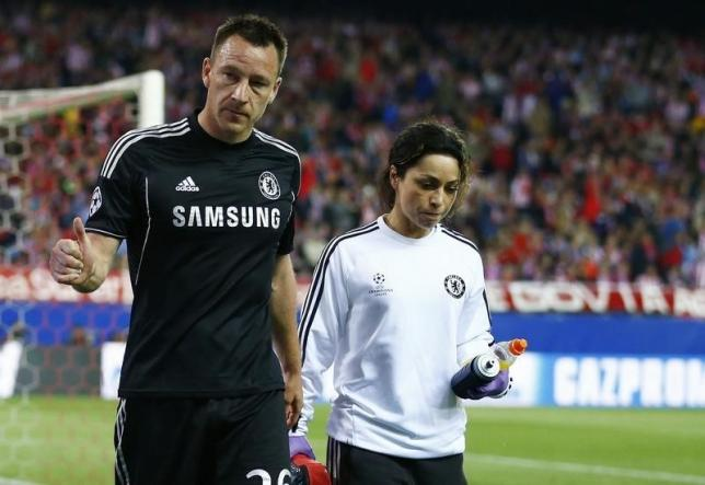Chelsea's captain John Terry is escorted off the pitch by the team doctor Eva Carneiro after being injured during their Champion's League semi-final first leg soccer match against Atletico Madrid at Vicente Calderon stadium in Madrid, April 22, 2014.    REUTERS/Darren Staples