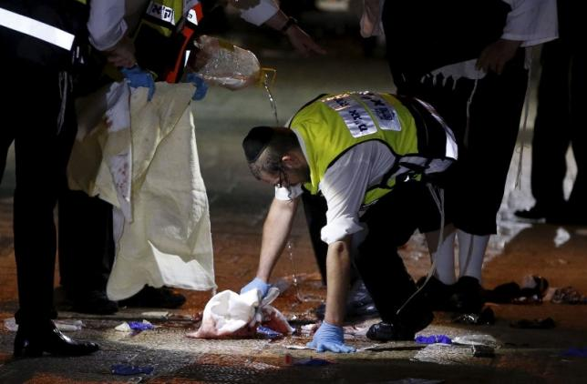 A member of the Zaka Rescue and Recovery team cleans blood stains at the scene where a Palestinian was shot dead after he stabbed and killed two people in Jerusalem's Old City October 3, 2015. Photo :REUTERS