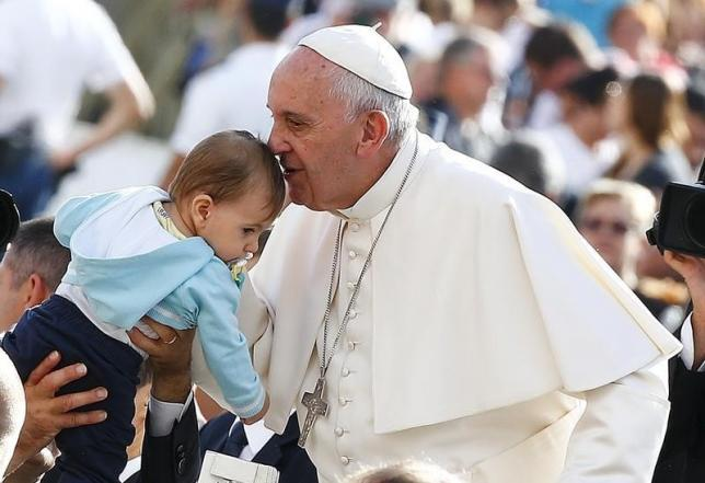 Pope Francis kisses a baby as he arrives to lead the weekly audience in Saint Peter's Square at the Vatican October 7, 2015. Photo:  REUTERS