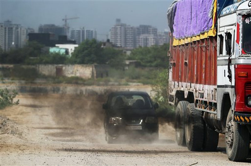 A truck gives out smoke as it drives past a car in New Delhi, India on Wednesday, September 23, 2015. Photo: AP