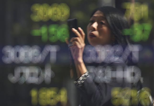 A woman using a smartphone is reflected on a stock quotation board outside a brokerage in Tokyo, Japan, September 29, 2015.  REUTERS/Issei Kato
