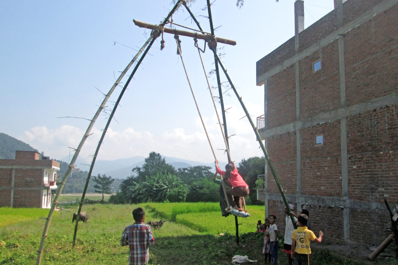 Children enjoying on the swing in Patenitar, Byas-8 of Tanahun district on Monday. Swings are one of the main attractions among people, especially children, in the 15-day long Dashain festival. Photo: Madan Wagle/ THT
