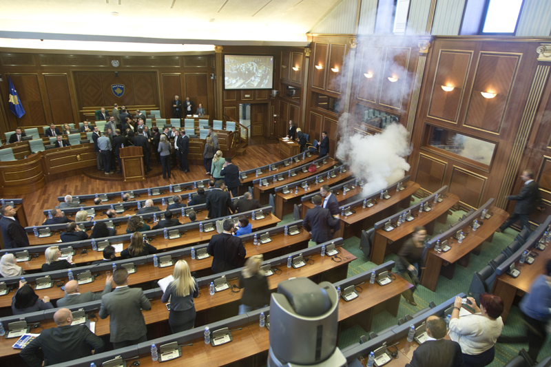 Kosovo lawmakers empty the chamber of Parliament as smoke billows from a tear gas canister thrown by opposition lawmakers in Kosovo disrupting Parliament's session, in the capital Pristina, Thursday, Oct. 15, 2015. Photo: AP
