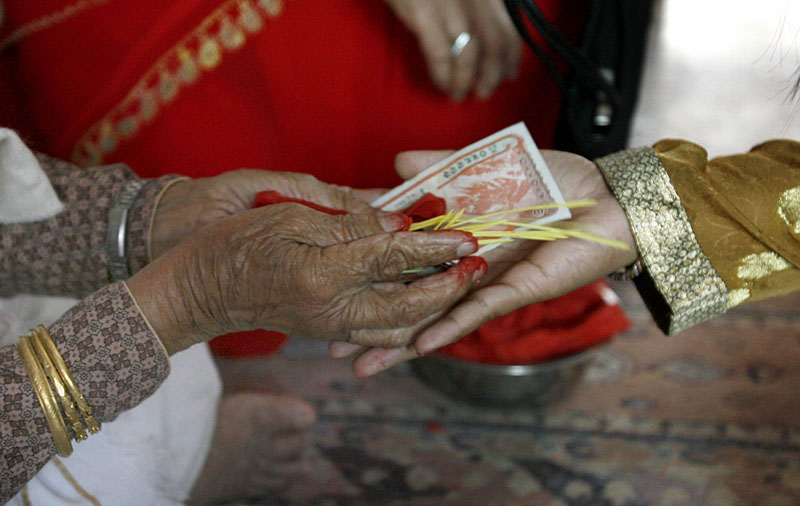 A girl takes money and offering after receiving tika in Kathmandu. Photo: Navesh Chitrakar