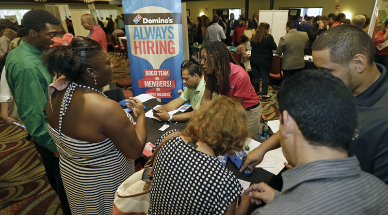 In this photo taken Wednesday, July 15, 2015, job seekers listen as Kaysara Mandry, center, talks about job opportunities at the Domino's booth during a job fair in Miami Lakes, Fla.  U.S. hiring slowed sharply and previous job gains were revised lower amid a broad slowdown in the global economy. The Labor Department says employers added just 142,000 jobs in September 2015 as manufacturers and oil drillers shed workers. Photo: AP