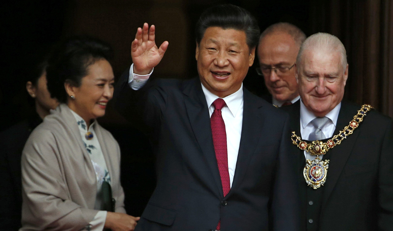 China's President Xi Jinping, centre, waves as he leaves after lunch with Britain's Prime Minister David Cameron at Manchester Town Hall in Manchester, England, Friday,  Oct. 23, 2015 on the final day of his state visit. in the background is his wife Peng Liyuan. Photo: AP