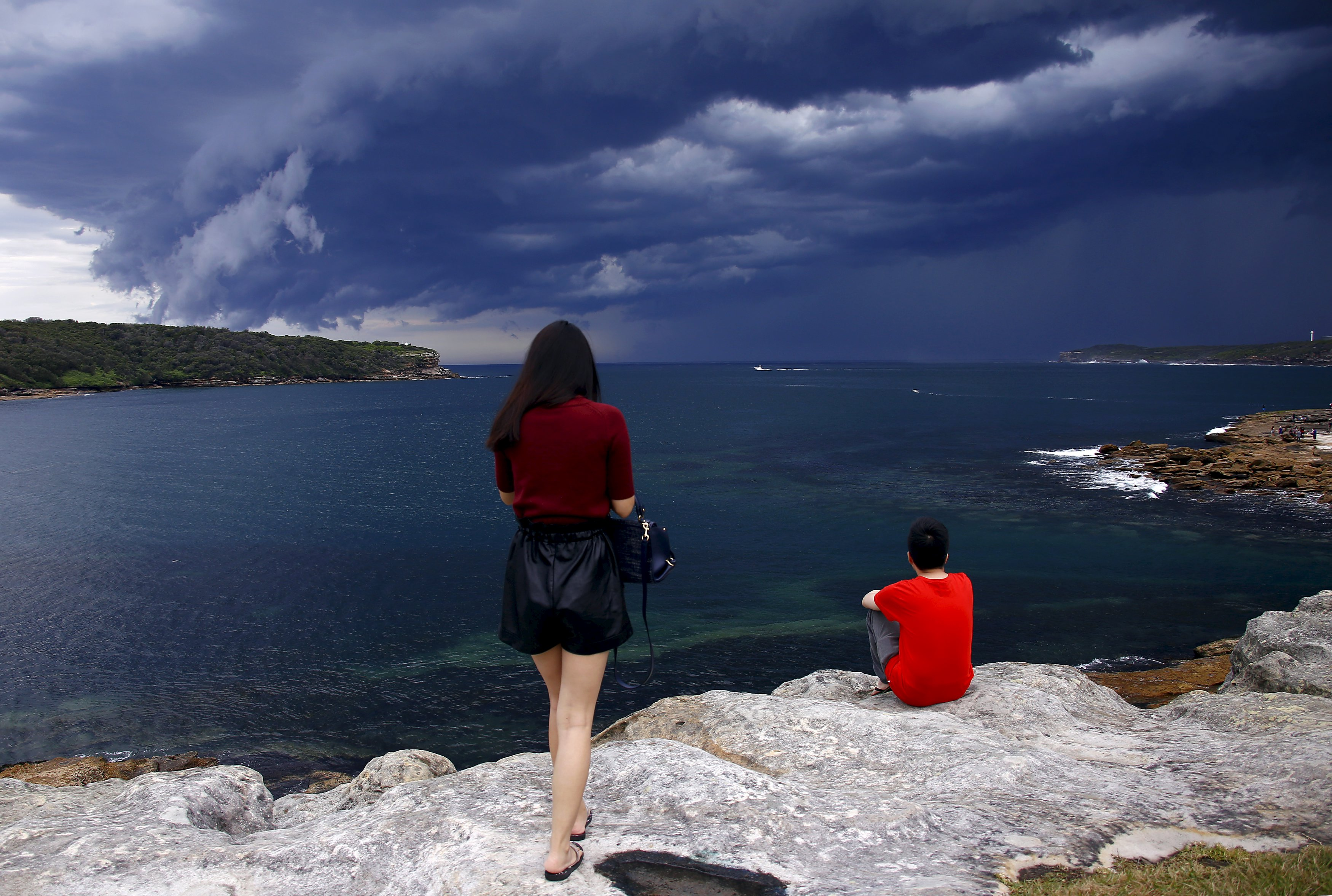 Chinese tourists watch storm clouds moving along the coast towards the city of Sydney, Australia, November 6, 2015. Photo: Reuters