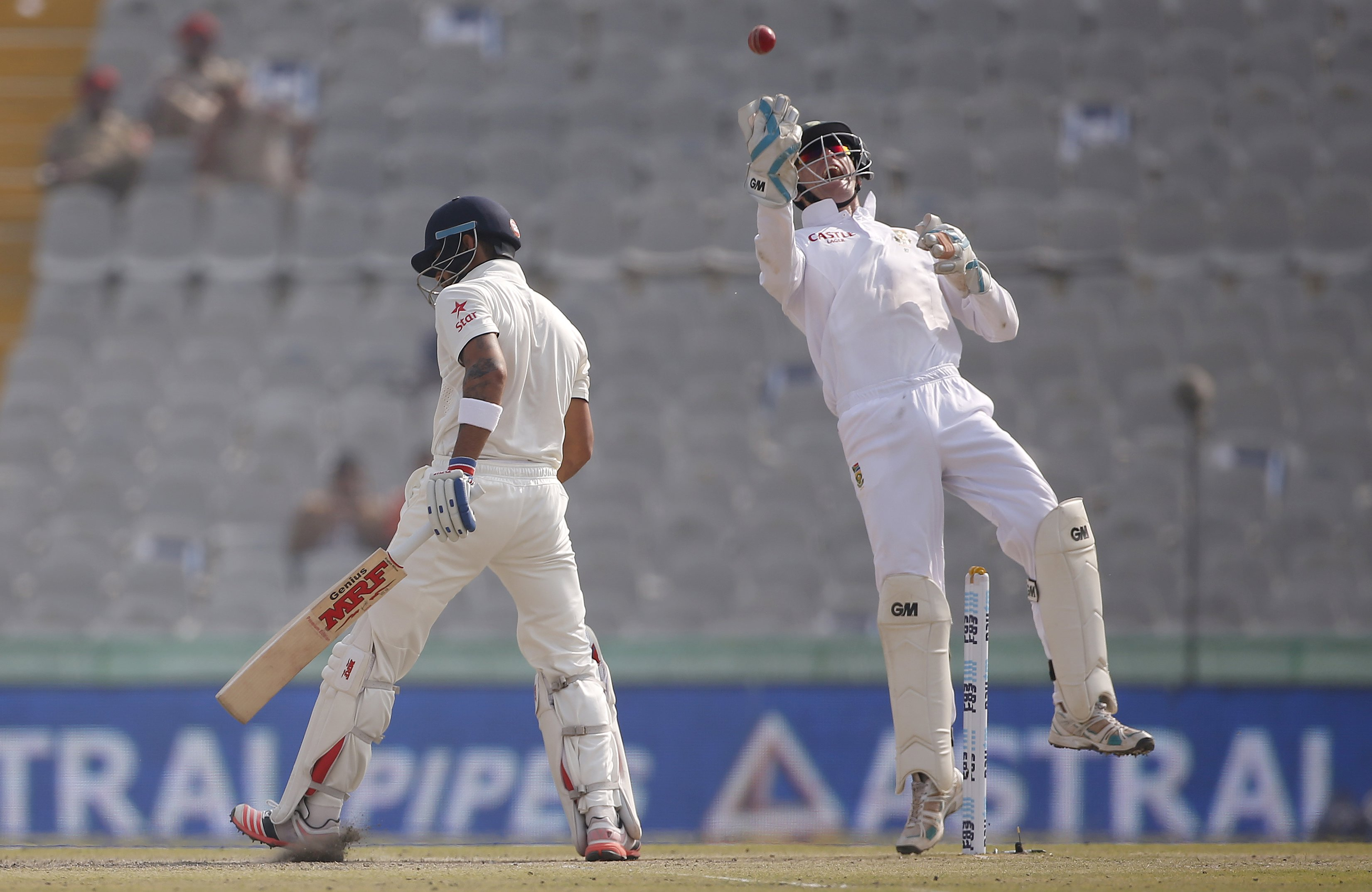 South Africa's wicketkeeper Dane Vilas (right) celebrates after taking a catch to dismiss India's captain Virat Kohli during the third day of their first cricket test match, in Mohali, India, November 7, 2015. Photo: Reuters