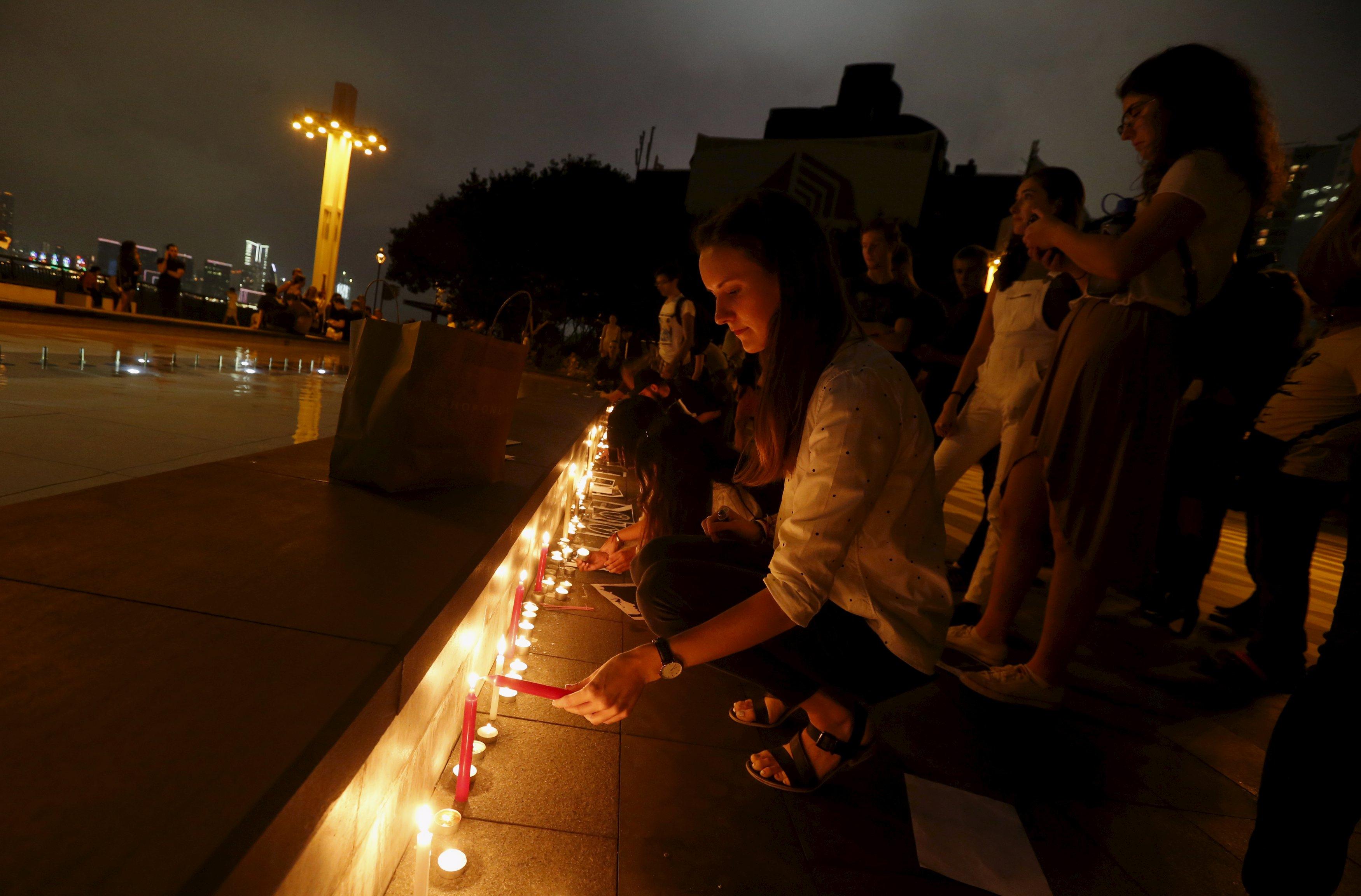 A participant lights up a candle during a vigil honoring the victims of the Paris attacks, in Hong Kong, China November 14, 2015.      REUTERS/Bobby Yip