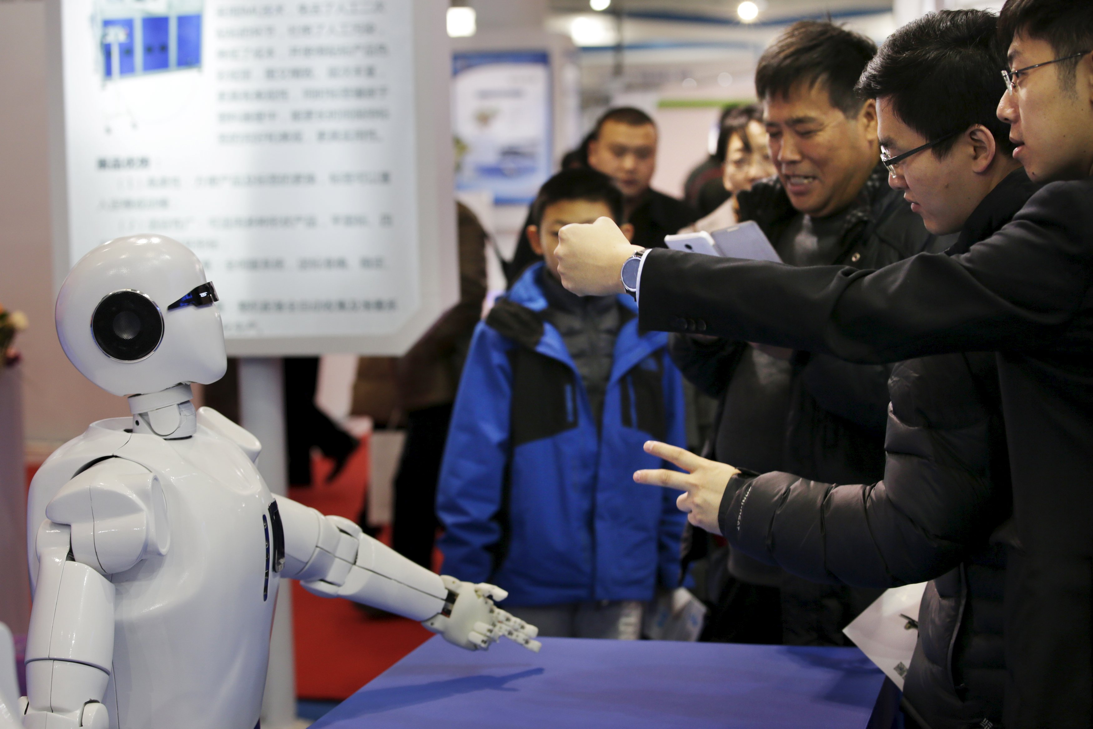 Visitors gesture to a KINGER Robot at the World Robot Exhibition during the World Robot Conference in Beijing, China, November 24, 2015. The conference, which kicked off in Beijing on Monday, is a three-day event including a forum, an exhibition and a robot contest for youths, Xinhua News Agency reported. Photo: Reuters