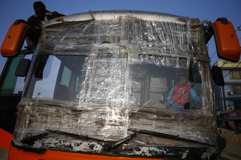 A child looks through a broken windshield of a long route passenger bus in Koteshwor, Kathmandu on Saturday, November 14, 2015. The windshield of the bus was broken after protesters demonstrating against the new Constitution threw stones while the bus was on its way to Kathmandu from the Tarai region. As the festival of Tihar ended, people are returning from Tarai regions to the city. Photo: Skanda Gautam