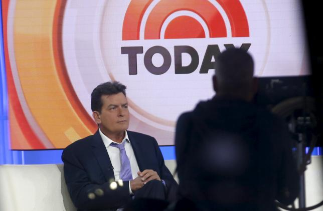 Actor Charlie Sheen is seen through a window as he sits on the set of the NBC Today show prior to being interviewed by host Matt Lauer in the Manhattan borough of New York City, November 17, 2015.   REUTERS/Mike Segar