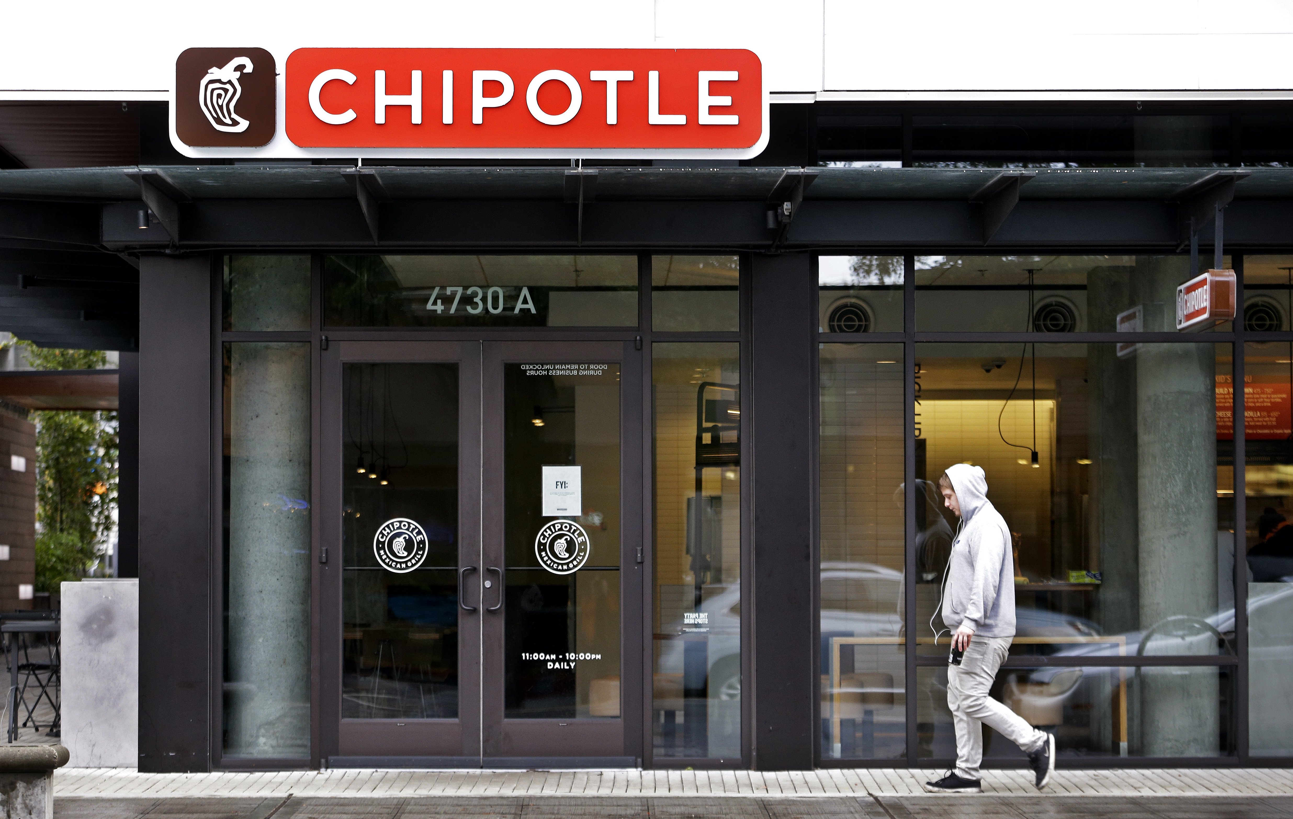 A pedestrian walks past a closed Chipotle restaurant Monday, November 2, 2015, in Seattle. Photo: AP