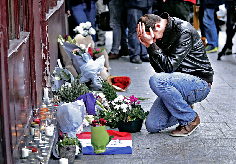 A man pays his respect outside the Le Carillon restaurant the morning after a series of deadly attacks in Paris , November 14, 2015.      REUTERS/Christian Hartman