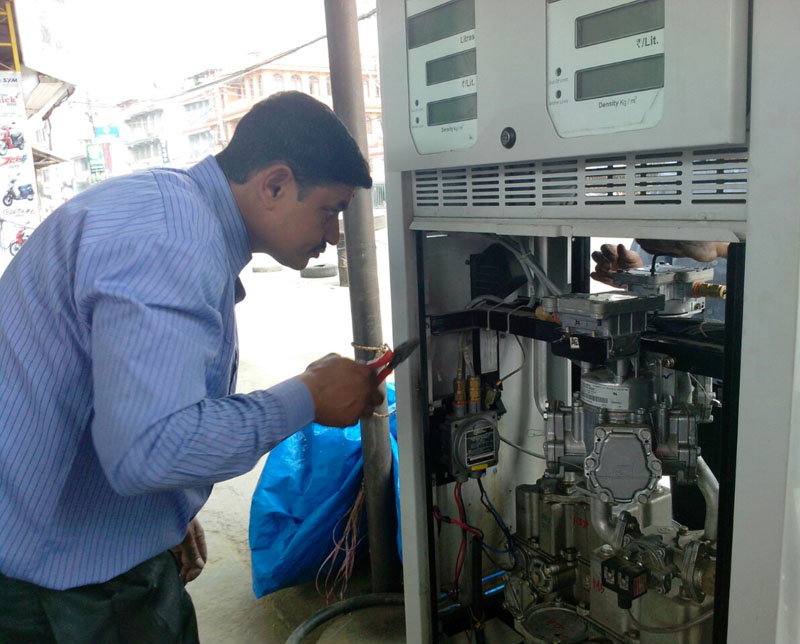 A technician examining a fuel dispenser machine in Pokhara on Friday, November 27, 2015. After the exposure of fraud committed by petrol pumps to cheat consumers using remote control and devices in the fuel dispenser in Kathmandu, a monitoring team comprising representatives from Nepal Bureau of Standard and Metrology, District Development Office and consumers decided to examine 43 petrol pump fuel dispensers. Photo: Rup Narayan Dhakal