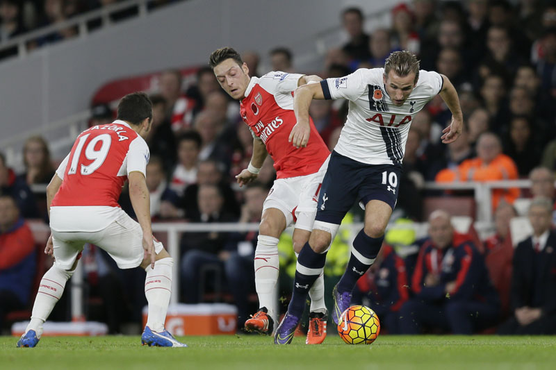 Arsenalu2019s Mesut Ozil, centre, competes for the ball with Tottenhamu2019s Harry Kane during the English Premier League soccer match between Arsenal and Tottenham Hotspur at the Emirates Stadium in London, Sunday Nov. 8, 2015. (AP Photo/Tim Ireland)