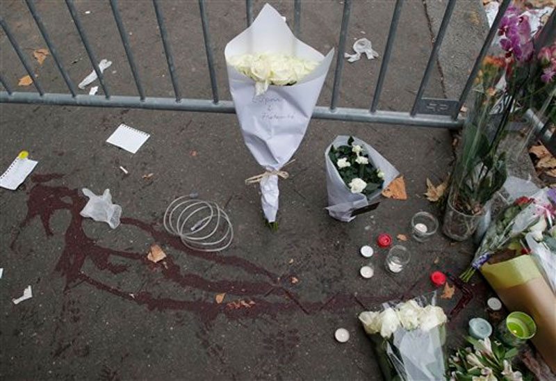 Cards, candles and flowers are placed outside the Bataclan concert hall in Paris, France on November 14, 2015. Photo: AP
