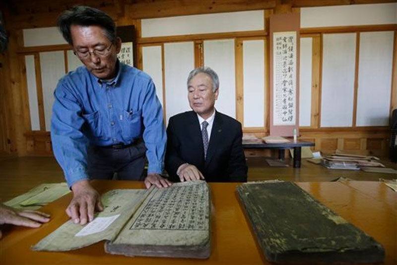 Hwang You Yeon, left, points at his familyu2019s two-volume gemological book written in 1723 at a museum commemorating one of his prominent ancestors in Paju, South Korea on October 13, 2015. Photo: AP