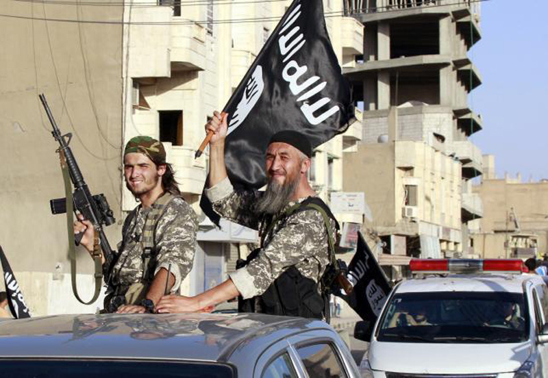 Islamic State fighters wave flags as they take part in a military parade along the streets of northern Raqqa province, Syria June 30, 2014. Photo: Reuters