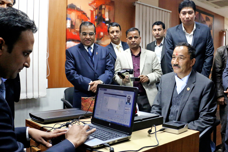 Minister for Foreign Affairs Kamal Thapa commencing the Live Enrollment System by replacing the Hand Written Passport on Monday, November 23, 2015. Photo: RSS