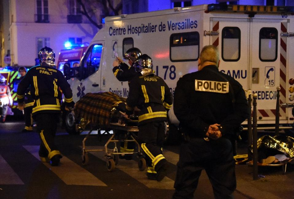 Firefighters evacuate an injured person near the Bataclan concert hall in central Paris, on November 14, 2015. Photo: AP