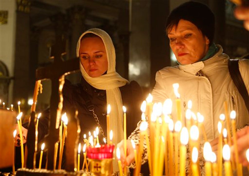 People light candles inside an Orthodox church in St.Petersburg during a day of national mourning for the plane crash victims, Russia, on Sunday, November 1, 2015. Photo: AP