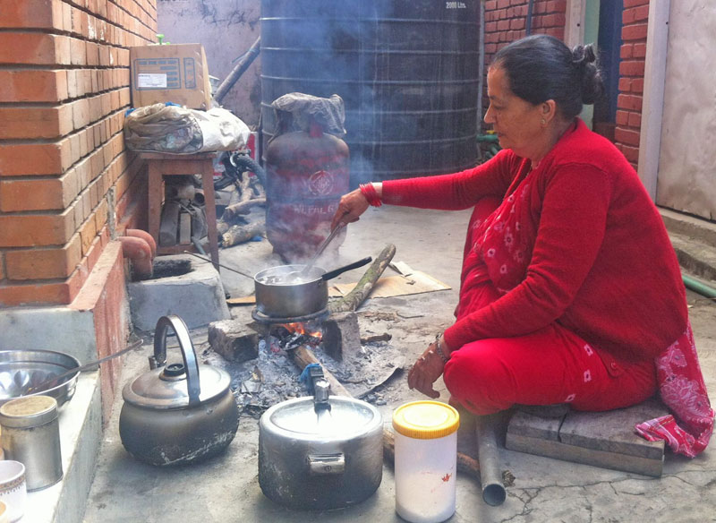 In this photograph that Nepali Congress leader Ram Chandra Paudel posted on Facebook, his wife Sabita Paudel is seen making tea on firewood at her backyard.