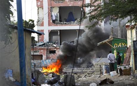 Somali men watch as fires burn amidst the destruction outside the Sahafi Hotel in Mogadishu, Somalia Sunday, Nov. 1, 2015. AP