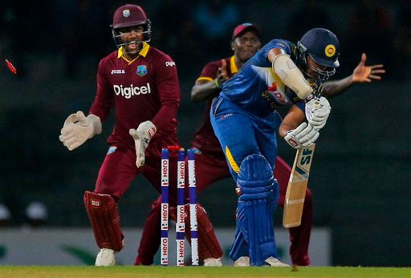 Sri Lanka's Shehan Jayasuriya (right) is bowled out by West Indies's Sunil Narine as wicketkeeper Denesh Ramdin, left, reacts during their first one day international cricket match in Colombo, Sri Lanka, Sunday, November 1, 2015. Photo: AP