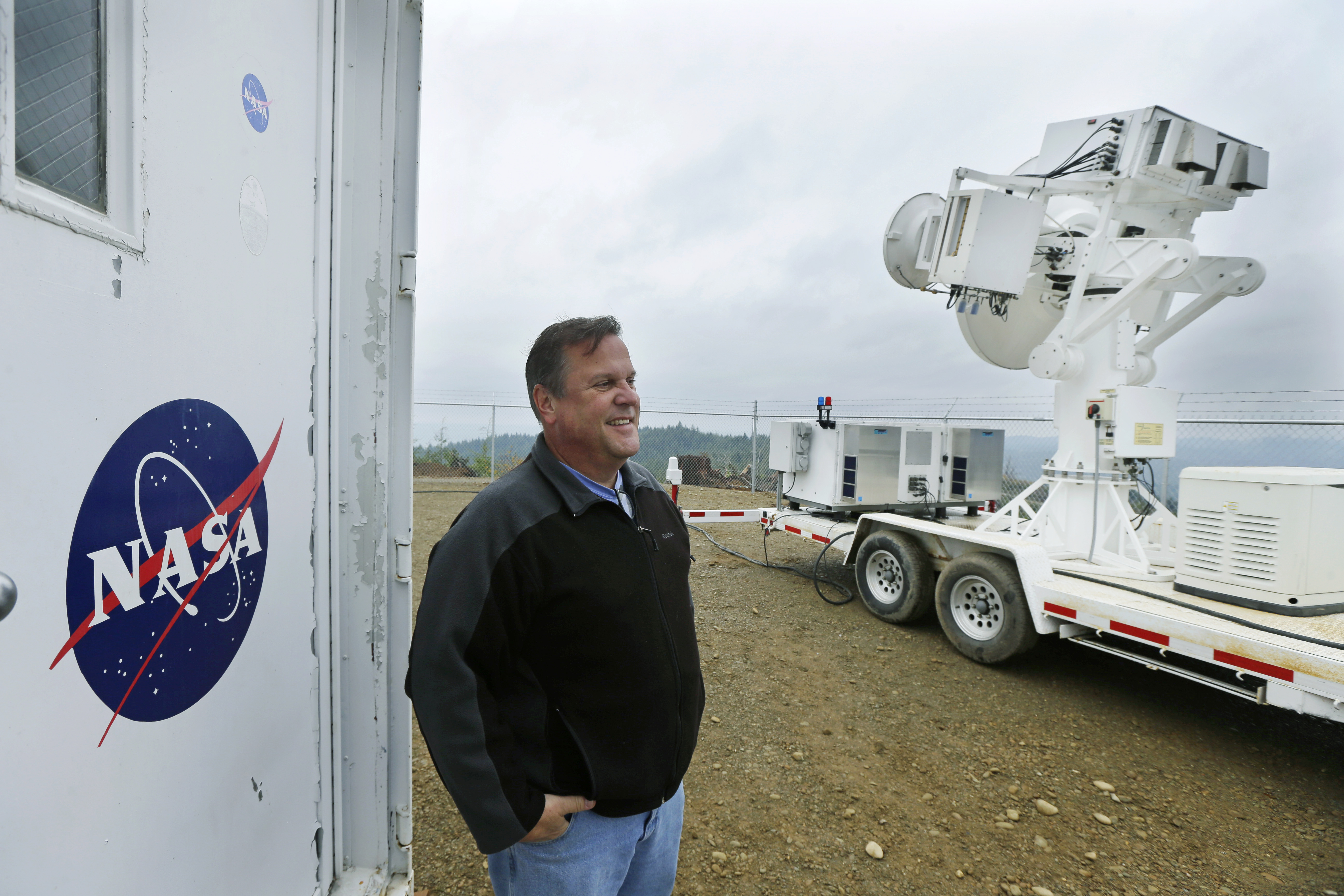 David Wolff, a research scientist with NASA, poses for a photo Friday, November 6, 2015, next to one of the large radar instruments installed on a hilltop near Moclips, Washington. Photo: AP