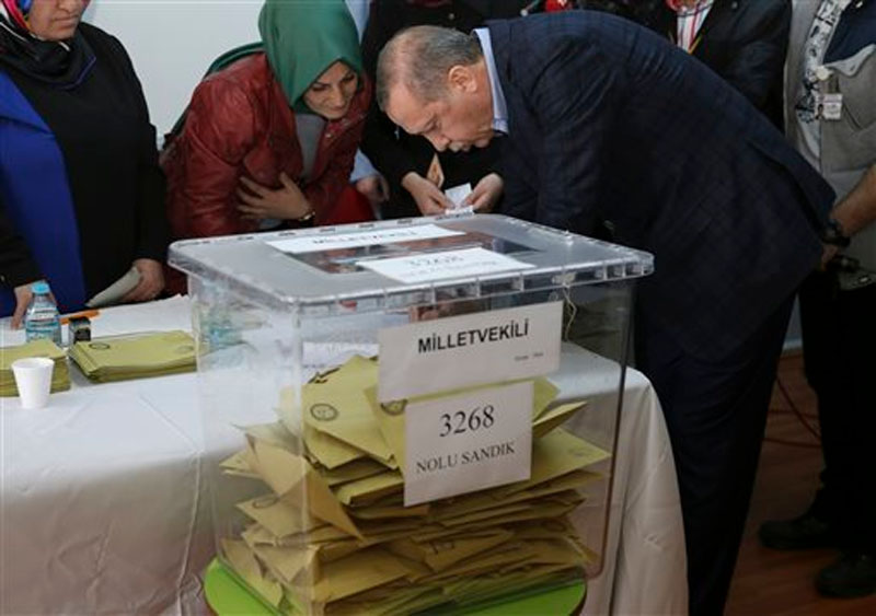 Turkey's President Recep Tayyip Erdogan (right) signs an official paper after he cast his vote at a polling station, in Istanbul on Sunday, November 1, 2015. Photo: AP