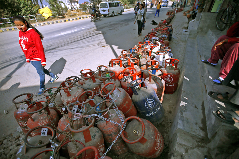 A woman walks past the lines of empty cooking gas cylinders waiting for fresh supply for five concesutive days in Kalopul, Kathmandu on Thursday, November 19, 2015. Photo: Skanda Gautam/ THT