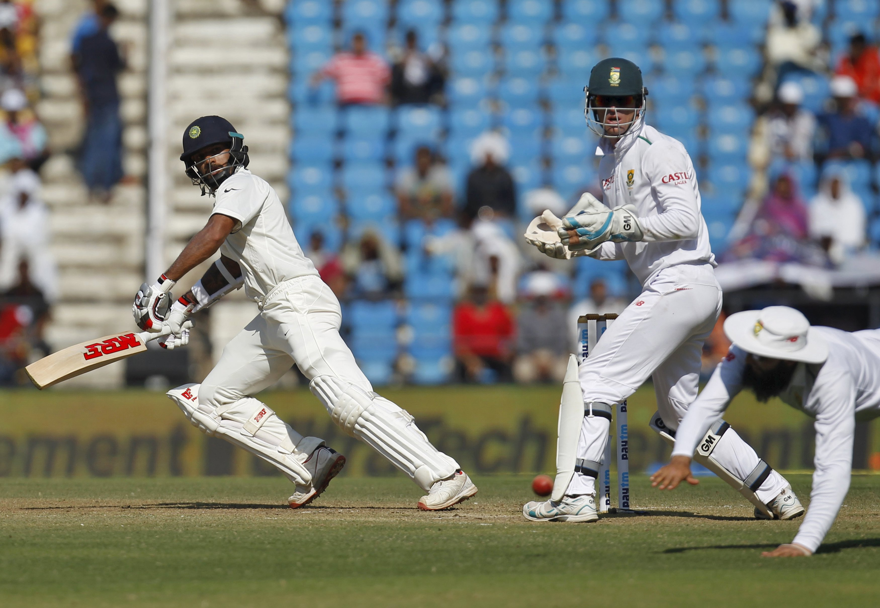 India's Shikhar Dhawan (left) plays a shot as South Africa's captain Hashim Amla dives unsuccessfully to stop the ball watched by wicketkeeper Dane Vilas during the second day of their third test cricket match in Nagpur, India, November 26, 2015. Photo: Reuters