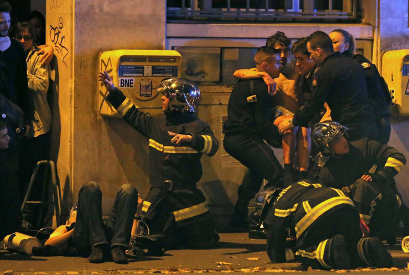 French fire brigade members aid an injured individual near the Bataclan concert hall following fatal shootings in Paris, France, November 13, 2015. Photo: REUTERS